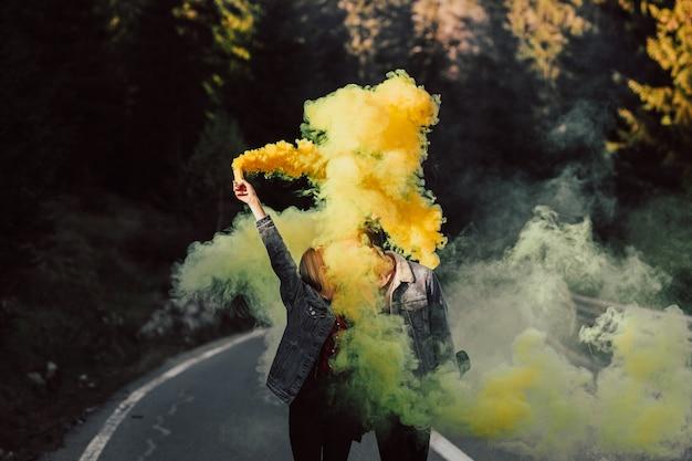 Bella bella coppia adorabile camminando sulla strada in montagna e tenendo in mano fumo colorato giallo e baciare.