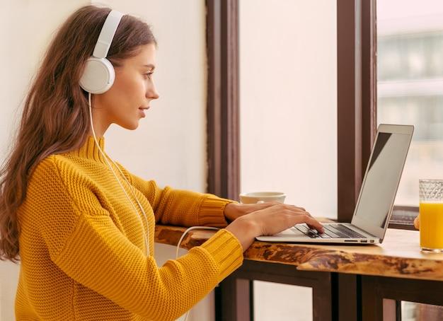 Bella bella donna con capelli lunghi biondi che lavora al computer portatile seduto a casa