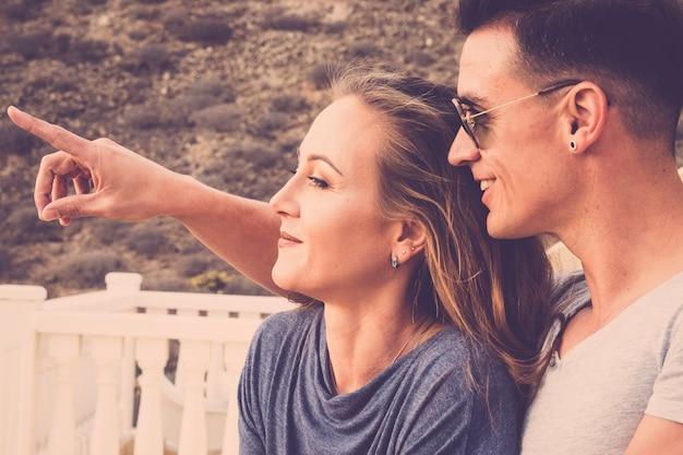 Bella coppia caucasica beuaitufl sorridere e guardare di fronte a loro. il giovane mostra alla signora qualcosa di lontano. giornata estiva con la luce del sole. filtro colori vintage. bella gente all'aperto sulla terrazza