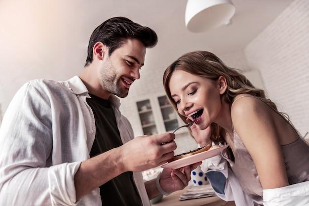 Buona colazione uomo barbuto dai capelli scuri con una camicia bianca che si sente benissimo mentre dà da mangiare alla sua bella moglie