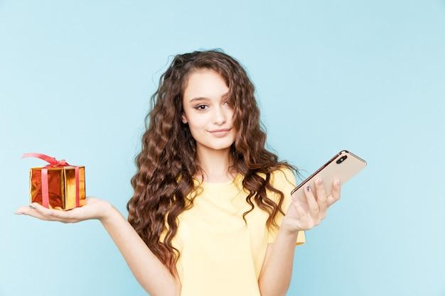 Bella donna bruna con regalo di compleanno e telefono isolato.