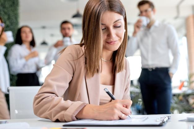 Simpatica signora d'affari che firma un contratto finanziario, mette firma per iscritto su carta aziendale legale compila il modulo del documento acquista un prestito assicurativo, stipula un accordo commerciale, vista ravvicinata. concetto di business