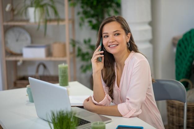 Bella imprenditrice impegnata seduto davanti al computer portatile mentre si tiene una conversazione telefonica