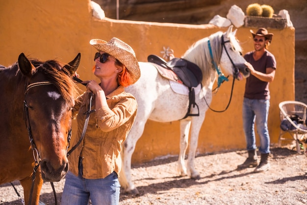 Bella coppia caucasica all'aperto prepara e controlla l'equipaggiamento del cavallo pronto per andare a vivere un nuovo viaggio d'avventura in modo alternativo alla scoperta di percorsi naturali e concetti di vita di campagna per i giovani