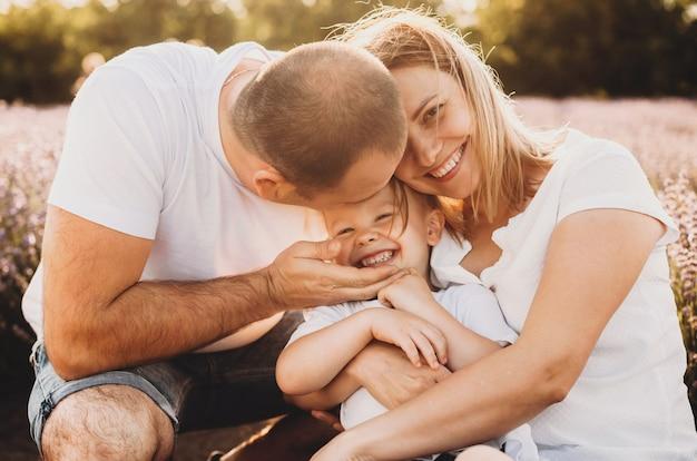 Una bella famiglia caucasica in posa in un campo di lavanda e abbraccia il loro bambino