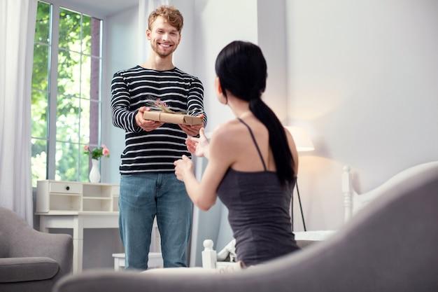 Bel uomo allegro che sorride mentre prepara una sorpresa per sua moglie