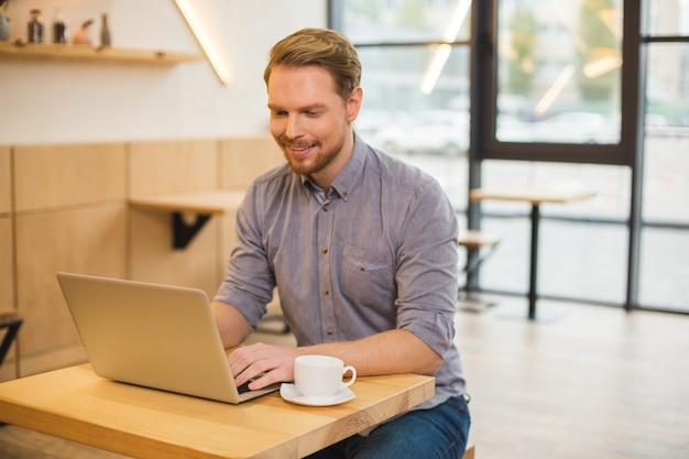 Bello allegro positivo uomo sorridente e guardando lo schermo del laptop durante la digitazione