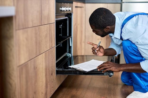 Bello tuttofare dell'appaltatore in tuta guardando all'interno del forno elettrico esaminando prima della riparazione durante la scrittura di informazioni sul forno, puntando il dito indice, seduto sul pavimento a casa in cucina.