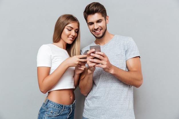 Bella coppia che guarda i telefoni