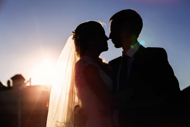 Sagome di bella coppia sul tramonto
