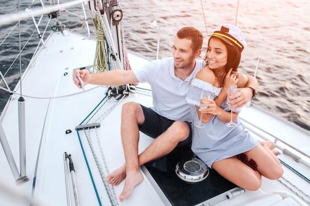 Bella coppia si siede insieme e ha bicchieri di champagne. il giovane prende selfie di lui e della fidanzata. pongono e sorridono. la donna ha il cappuccio sulla testa.
