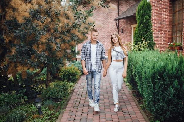 Bella coppia che cammina insieme vicino alla casa. amato tenendosi per mano e sorridendo alla telecamera.