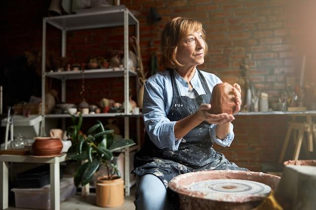 Simpatica artigiana in grembiule che modella l'argilla e sorride mentre è seduta su una panchina con ruota di ceramica