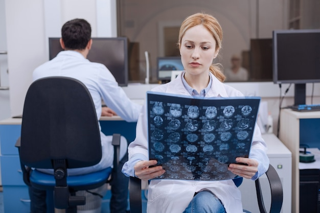 Bella dottoressa carina che tiene un'immagine a raggi x e la esamina mentre mette una diagnosi