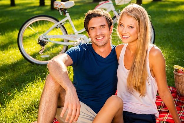 Una bella giornata per il picnic. felice giovane coppia di innamorati che si rilassano nel parco insieme mentre sono seduti su una coperta da picnic e sorridono mentre la bicicletta sta in piedi sullo sfondo