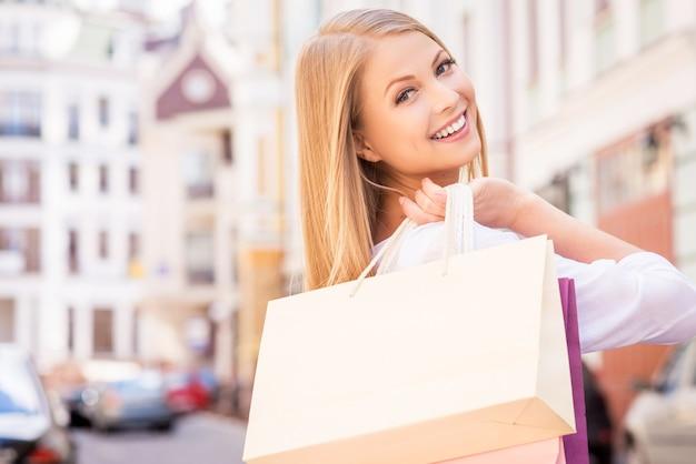 Bella giornata per lo shopping. vista posteriore di una bellissima giovane donna allegra che tiene in mano le borse della spesa e si guarda alle spalle mentre sta in piedi all'aperto