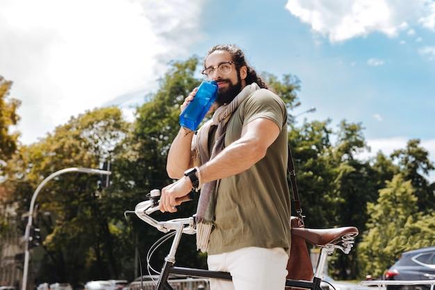 Bel uomo felice in piedi vicino alla sua bicicletta mentre beve l'acqua
