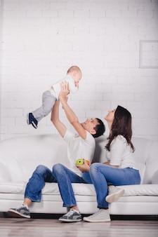 Bella famiglia in sfondo studio in interni moderni leggeri al chiuso. sorridente giovane madre e padre con figlio bambino in posa insieme e seduto sul divano.