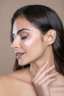 Bella sensazione. profilo di bel viso femminile con palpebre cadenti con crema sulla guancia e mano vicino al collo
