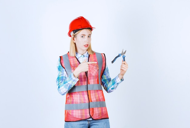 Simpatica maestra bionda con un elmetto rosso che punta le pinze che tiene nell'altra mano