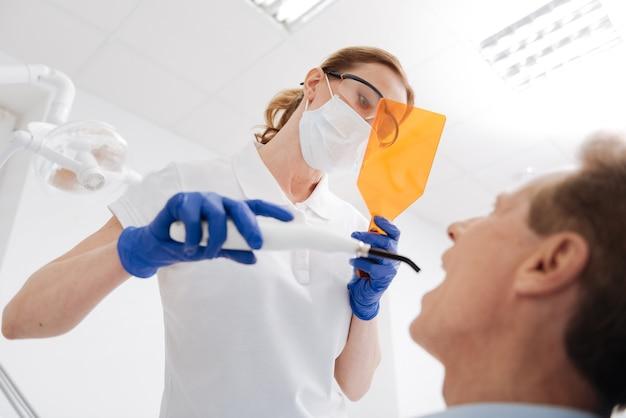 Bella dottoressa eccellente e concentrata che fa il suo lavoro e impiega attrezzature professionali per sbiancare i denti dei pazienti