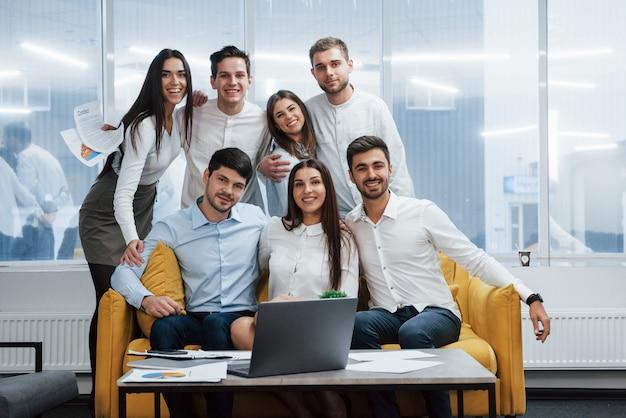 Bella atmosfera amichevole. ritratto di giovane squadra in abiti classici nel moderno ufficio illuminato