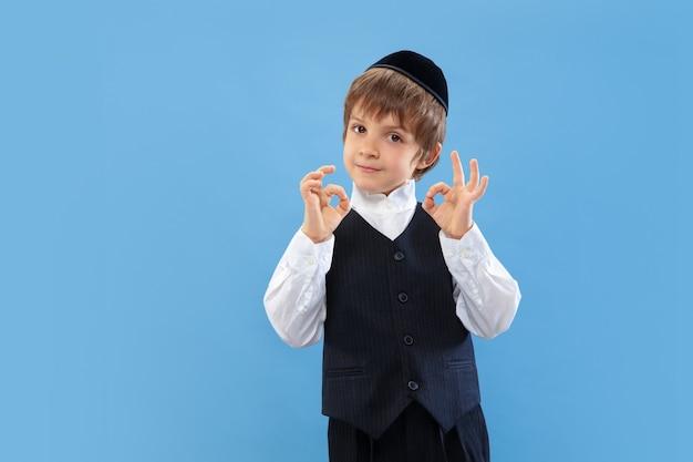 Bel gesto. ritratto di un giovane ragazzo ebreo ortodosso isolato sulla parete blu. purim, affari, festival, vacanze, infanzia, celebrazione pesach o pasqua ebraica, ebraismo, concetto di religione.