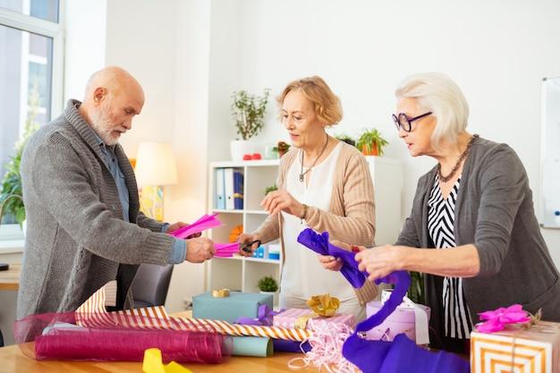 Bei regali. simpatiche persone anziane di bell'aspetto che confezionano regali mentre preparano sorprese per i loro amici