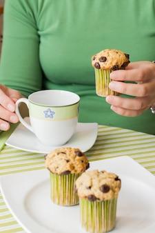 Bella mano della ragazza che prende un delizioso muffin con gocce di cioccolato a colazione in una tovaglia a strisce verdi