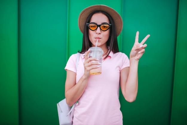 Bella ragazza si alza e mostra il simbolo del pezzo con le dita e tiene in mano una tazza di bevanda fredda. beve con la cannuccia. isolato sulla parete verde.