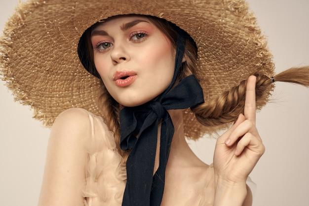 Bella ragazza con un cappello di paglia con un nastro nero e un vestito su una luce