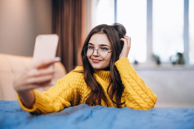 Bella ragazza con gli occhiali e maglione carino sta prendendo selfie