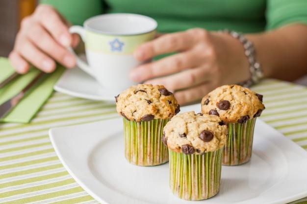 Bella ragazza con una tazza e un delizioso muffin al cioccolato a colazione con una tovaglia a strisce verdi