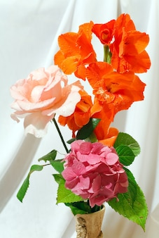 Bel bouquet estivo di gladiolo, ortensie e rose su sfondo di panno bianco