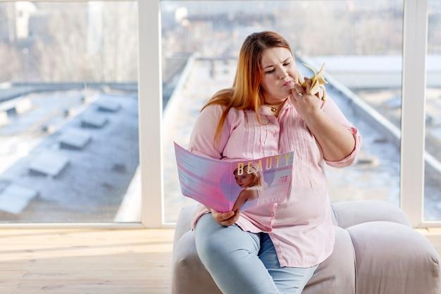 Bella donna di bell'aspetto che mangia uno spuntino mentre si sente molto affamato