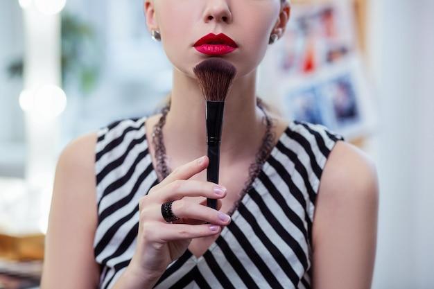 Bella donna di bell'aspetto che si tocca il mento con un pennello da trucco makeup