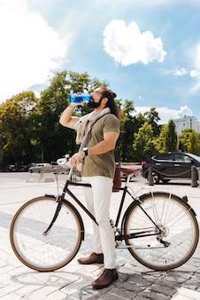 Uomo bello bello che tiene una bottiglia con acqua mentre beve da esso
