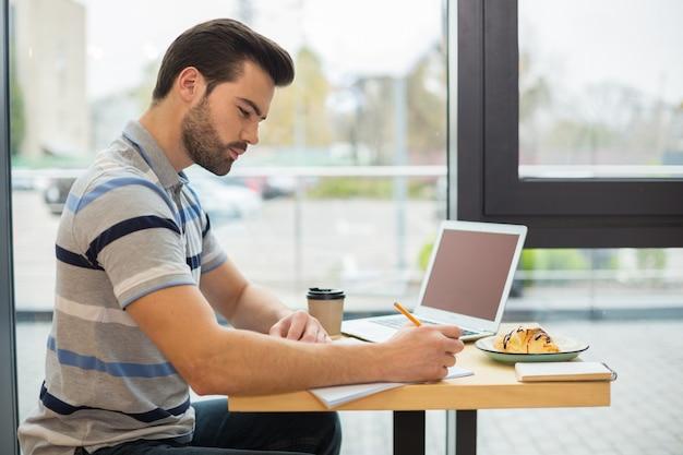 Bel bell'uomo intelligente seduto davanti al laptop e prendere appunti mentre si lavora