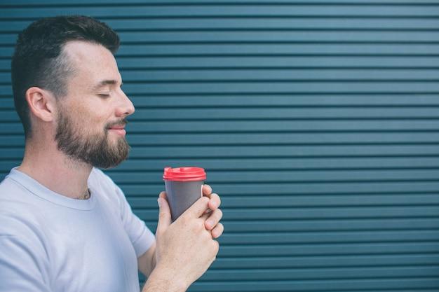 La persona piacevole e felice sta tenendo la tazza di caffè con entrambe le mani. lui sta sorridendo. guy sta tenendo gli occhi chiusi. isolato su strisce