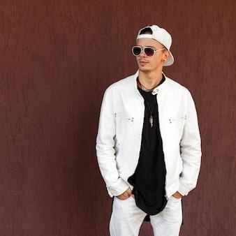 Bel giovane hipster in una giacca estiva bianca alla moda in un'elegante maglietta nera in un berretto da baseball alla moda in occhiali da sole scuri vicino a un muro vintage