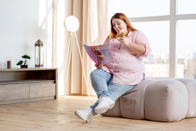 Bella donna affamata che tiene una banana mentre legge una rivista a casa