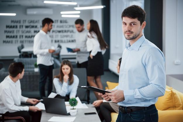 Interni belli. il ritratto di giovane tipo sta nell'ufficio con gli impiegati a fondo