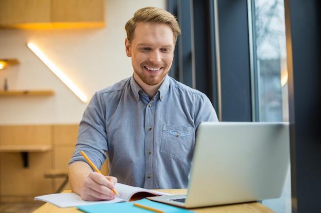 Bello allegro allegro uomo seduto al tavolo e guardando lo schermo del laptop mentre si lavora