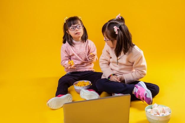 Bello e gentile. piccoli gemelli adorabili che si siedono sul pavimento nudo con marshmallow e patatine mentre guardano film sul computer portatile