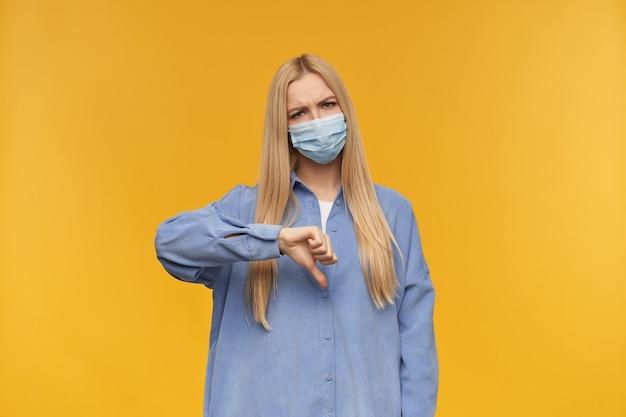 Bella donna, bella ragazza con lunghi capelli biondi mostra il segno del pollice verso il basso. indossare maglietta blu e mascherina medica. guardando in copia spazio, isolato su sfondo arancione