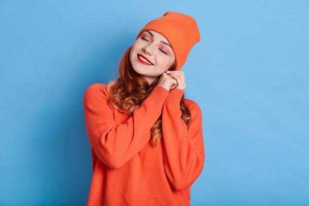 Bella donna sorride a trentadue denti, tiene le mani vicino all'orecchio, indossa un cappello e un maglione arancioni, gode di calore nei vestiti nuovi