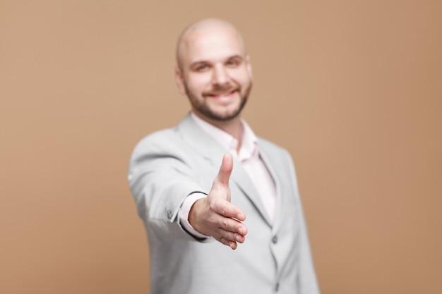 Piacere di conoscerti. felice toothy sorridente bello di mezza età barbuto calvo uomo d'affari in classico abito grigio in piedi e dando stretta di mano. girato in studio al coperto, isolato su sfondo marrone chiaro.