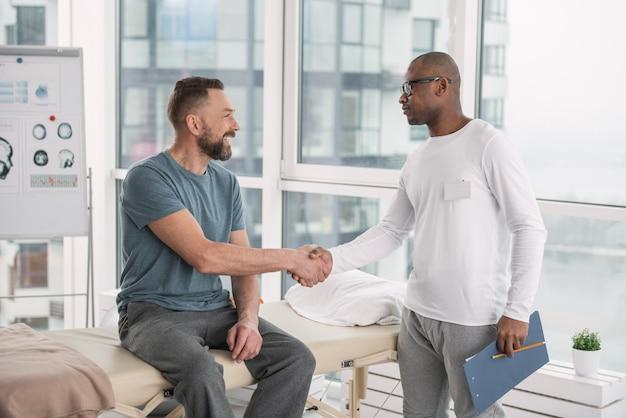 Piacere di conoscerti. joyful positivo paziente e medico si stringono la mano mentre si guardano l'un l'altro