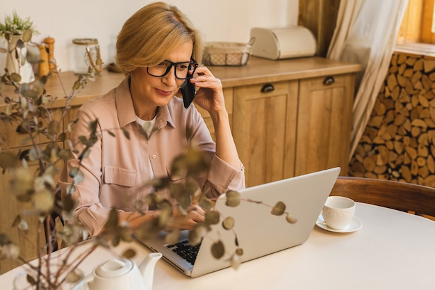 Buona mattinata. allegra donna anziana sorridente in piedi in cucina e usando il suo computer portatile mentre riposa dopo colazione, libero professionista che lavora a casa. utilizzo del telefono cellulare.
