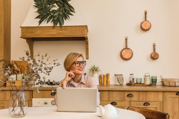 Buona mattinata. allegra donna anziana sorridente in piedi in cucina e usando il suo computer portatile mentre riposa dopo colazione, libero professionista che lavora a casa.